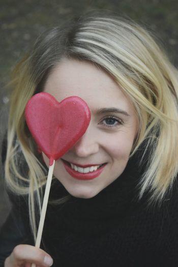 Close-Up Portrait Of Smiling Woman With Heart Shape Lollipop