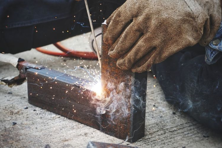 Close-Up Of Male Welder Welding In Factory