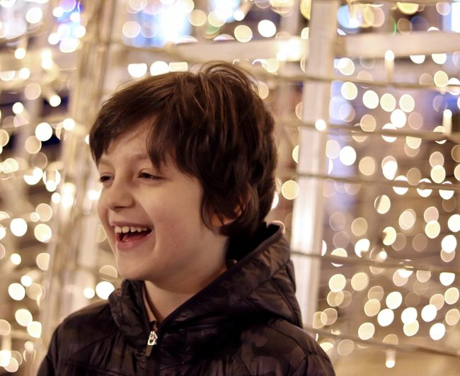 Close-up of cheerful boy looking away against illuminated lights