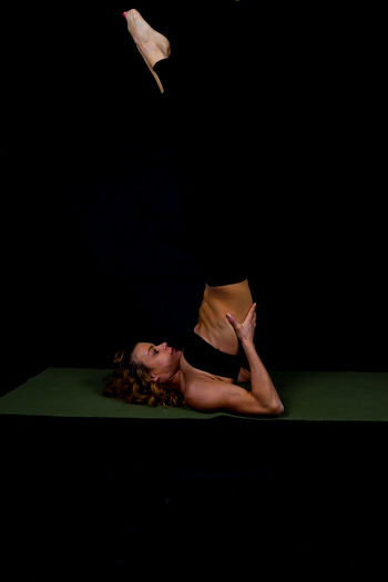 Athlete doing shoulder stand on exercise mat against black background