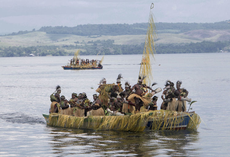 Tribal people in lake sentani against mountain