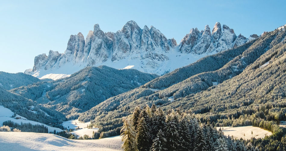 Alpine mountains with white snow and blue sky in dolomites ski resort in tyrol, italy.