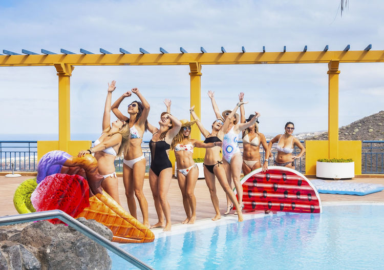 Female friends wearing bikinis enjoying at poolside