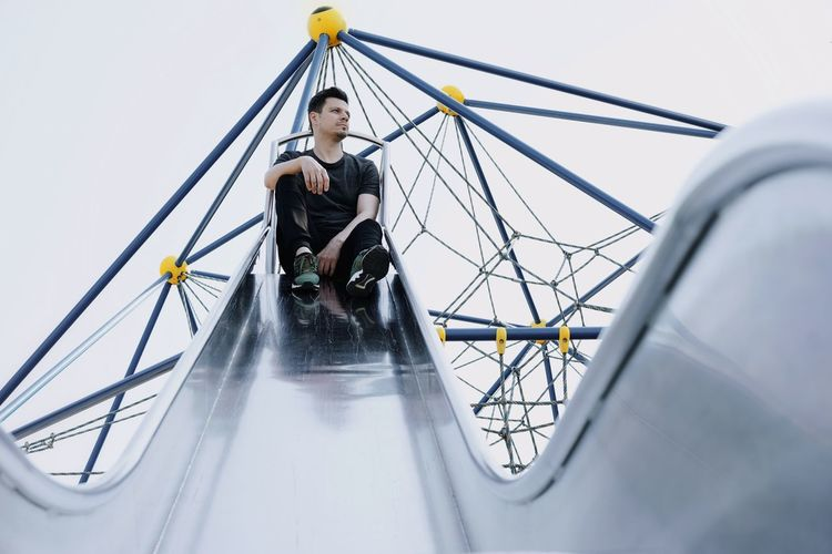 Low angle view of man sitting on slide against sky
