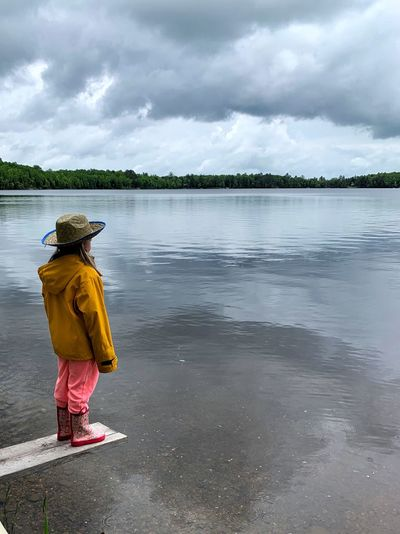 Rear view of woman in lake against sky