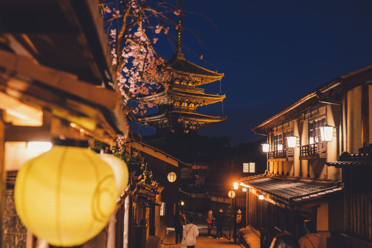 Low angle view of illuminated lanterns hanging outside building against sky at night