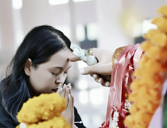 Woman Praying In Front Of Idol