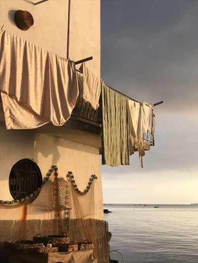 Clothes hanging on roof of building by sea against sky