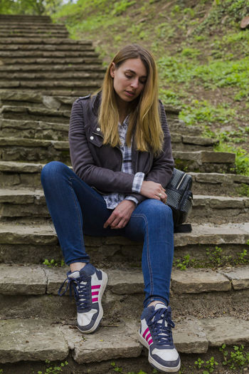 Sitting One Person Full Length Staircase Front View Young Adult Real People Lifestyles Casual Clothing Young Women Leisure Activity Architecture Day Long Hair Steps And Staircases Hair Outdoors Hairstyle Teenager Jeans Contemplation Adolescence