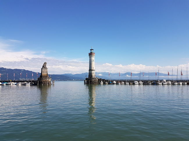 A couple of days here in Lindau would be fun. View of Lindau harbor with its Bavarian Lion Statue and the stone Lindau Lighthouse . Lakeconstance Bodensee