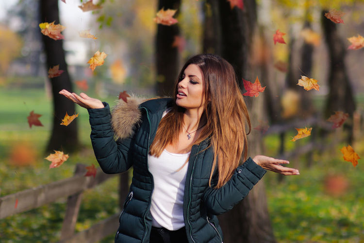 Joka Autumn Beautiful Woman Beauty In Nature Casual Clothing Day Flower Focus On Foreground Front View Happiness Jacket Leaf Leisure Activity Lifestyles Long Hair Nature One Person Outdoors Real People Smiling Standing Tree Waist Up Warm Clothing Young Adult Young Women