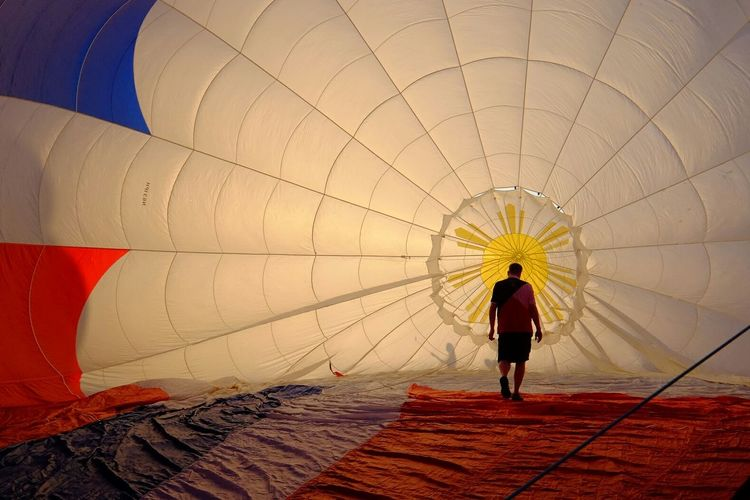 Rear view of man walking in hot air balloon