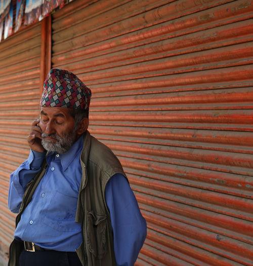 Senior Man Wearing Dhaka Topi Listening To Mobile Phone Against Shutters