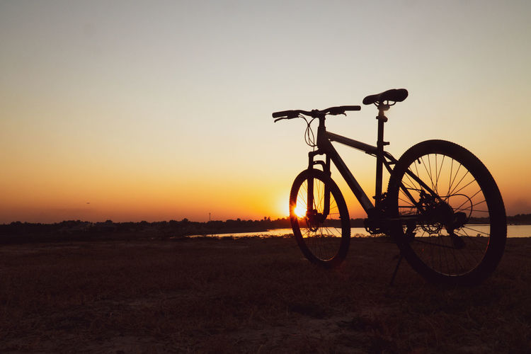 Silhouette bicycle on field against sky during sunset