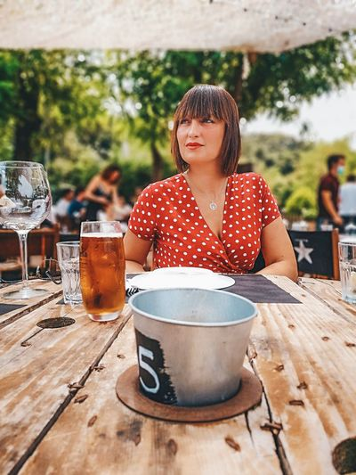 Woman looking away while sitting by table at restaurant