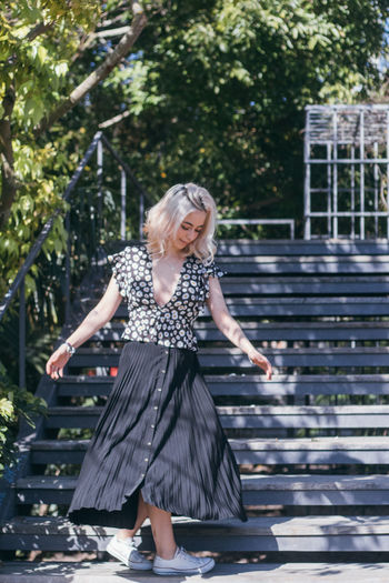 Full length of young woman standing on steps in park
