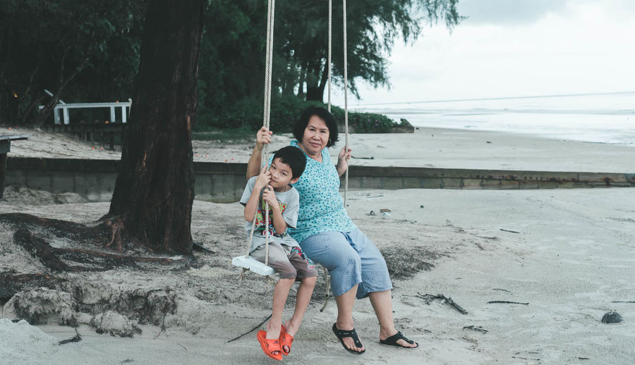 Full length portrait of woman sitting with grandson on swing at beach