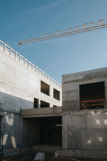 Low angle view of construction site against sky in city