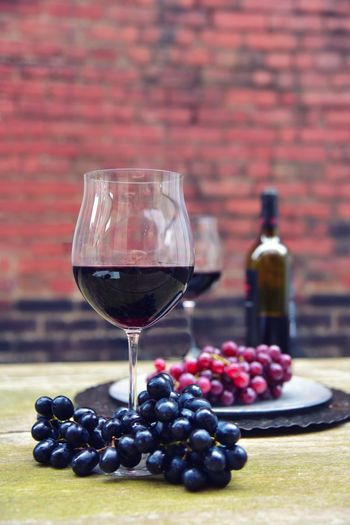 Wines With Grapes Served On Table Against Brick Wall