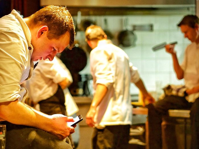 Side View Of Chef Using Phone In Kitchen