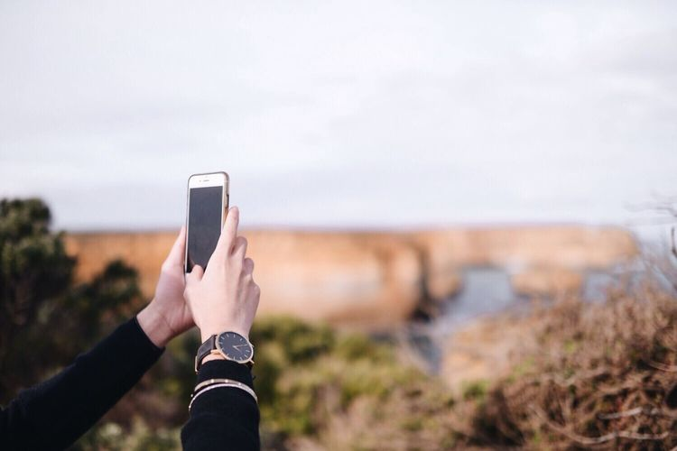Cropped image of woman hands photographing through smart phone