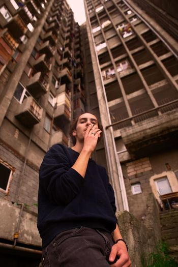 Low angle view of young man standing against building