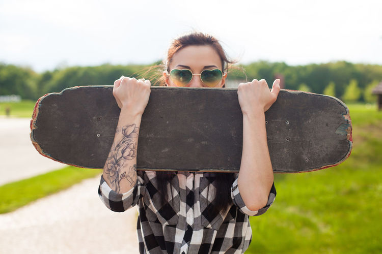 The woman with tattoo and in cool glasses is hidding her face with a skate on the background of park. Obscured Face Outdoors Waist Up Sunlight Looking At Camera Nature Fashion Casual Clothing Portrait Glasses Young Adult Lifestyles Day Focus On Foreground Real People Leisure Activity Standing Holding Front View One Person Sunglasses Women Adult Teenager