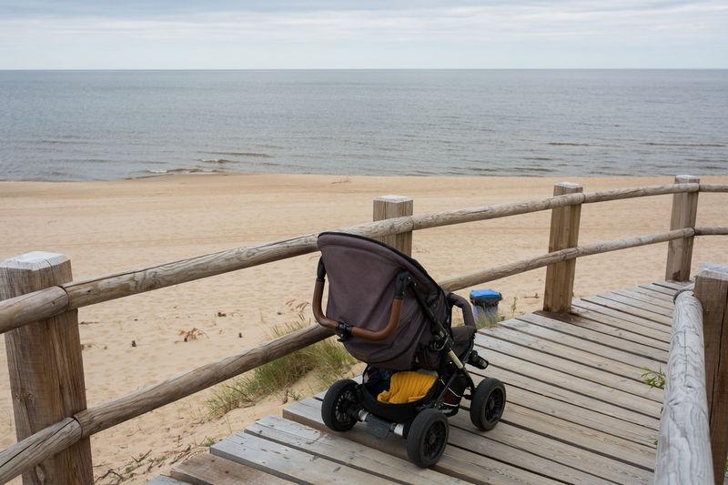 Baby stroller on boardwalk against sea
