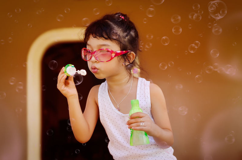Cute girl blowing soap bubbles in the air Playing Child Kid One Person Blowing Bubbles Sunglasses Young Girl Casual Clothing Girl Bubbles Happiness Playing Alone EyeEm Selects Bubble Wand Eyeglasses  Young Women Party - Social Event Beauty Portrait Headshot Beautiful Woman Waist Up Bubble Blowing Soap