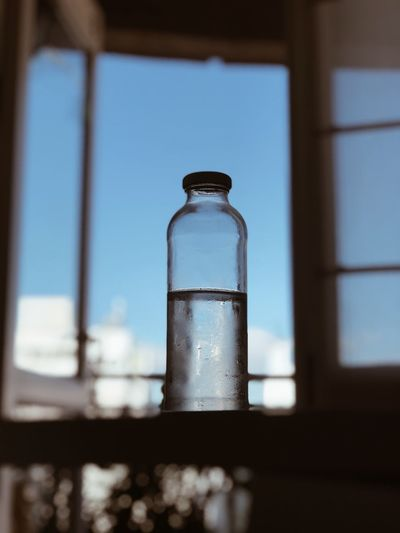 Water selects Healthy Eating Glass - Material Transparent Bottle No People Focus On Foreground Window Day Built Structure Food And Drink Reflection Water Container Low Angle View Indoors  Glass Close-up Nature Sky Blue
