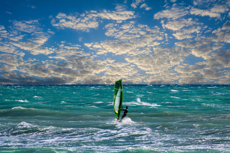 Person windsurfing in sea against sky
