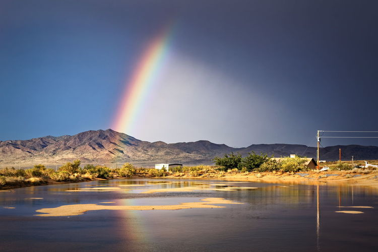 Scenic View Of Mountains Against Rainbow In Sky