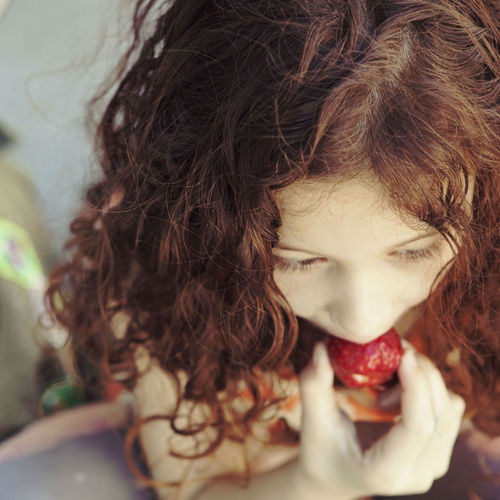 Close-Up Of Young Girl Eating Strawberry