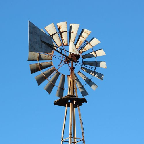 Low angle view of american-style windmill against clear blue sky