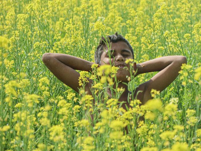 Portrait of boy on yellow flowering plants on field