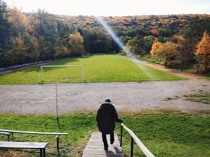 Rear view of man on steps against soccer field during autumn