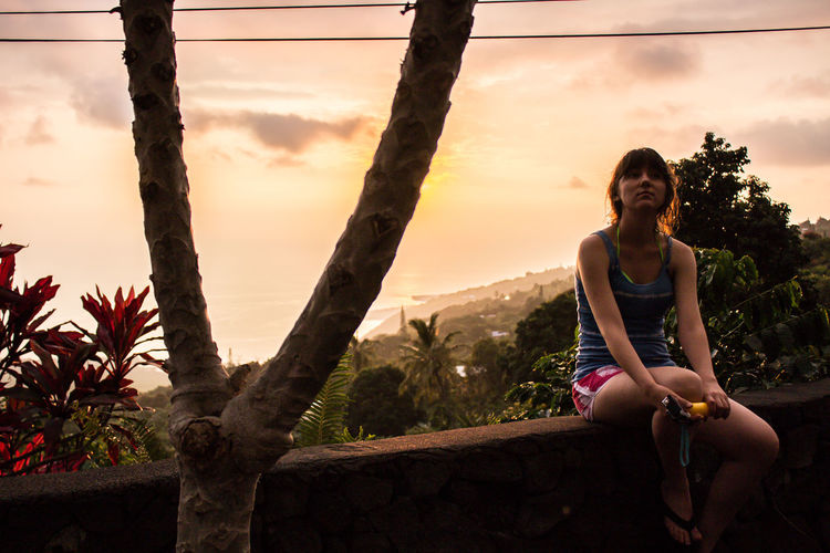 Woman looking up while sitting on retaining wall during sunset