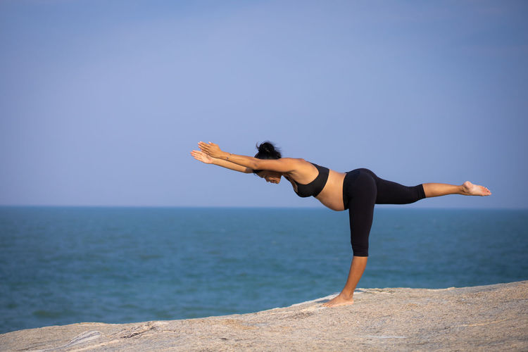 Full length of young woman exercising yoga on rock against sea against sky