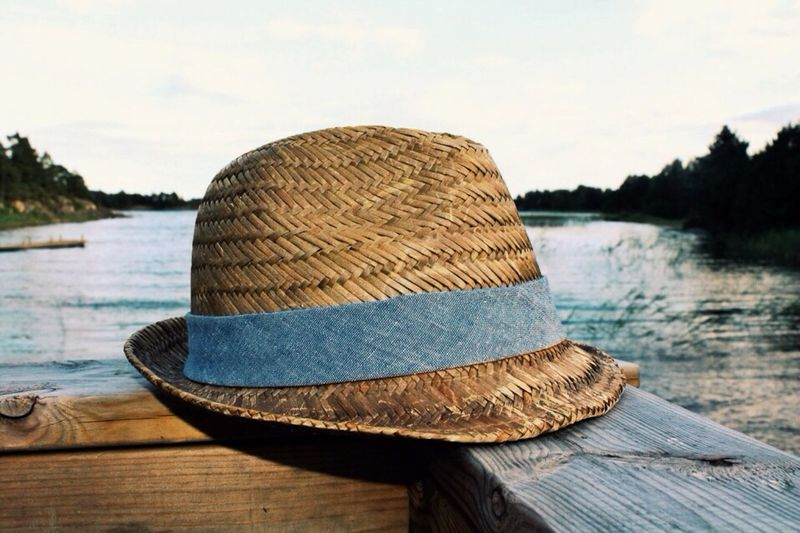 Straw Hat On Wooden Railing Against Lake