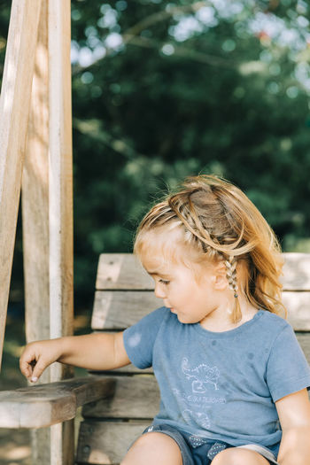 Girl looking away while sitting on wood