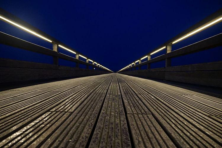 Surface level of footbridge against clear sky