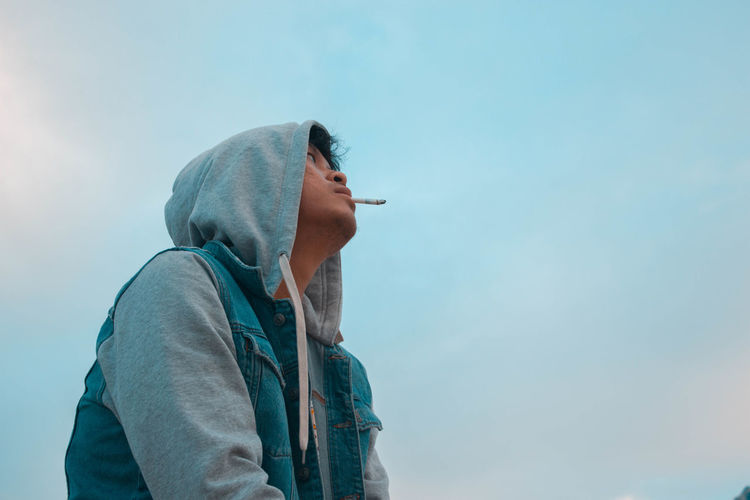 Low angle view of man smoking cigarette against sky