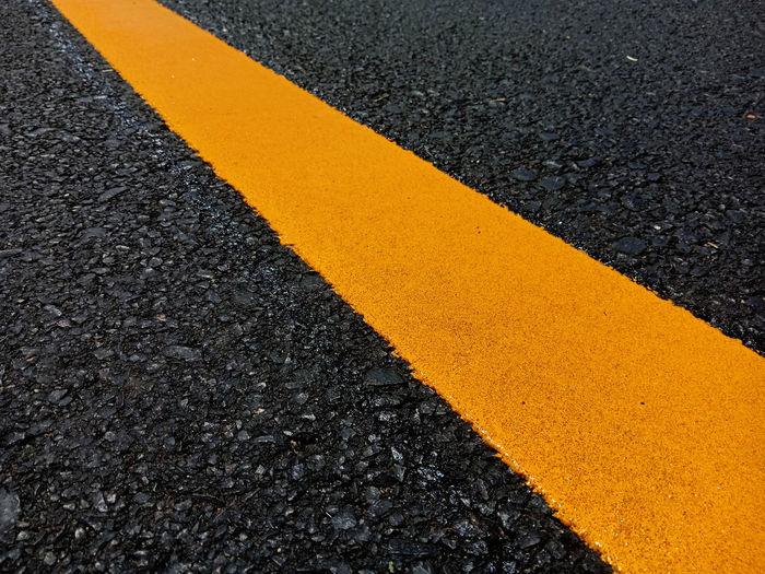High angle view of yellow line on asphalt
