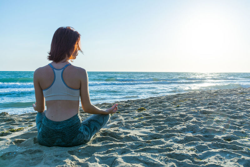 Rear View Of Woman Meditating At Beach Against Clear Sky