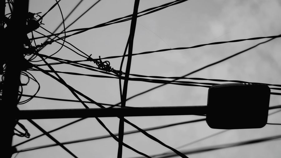 Low angle view of silhouette cables against sky