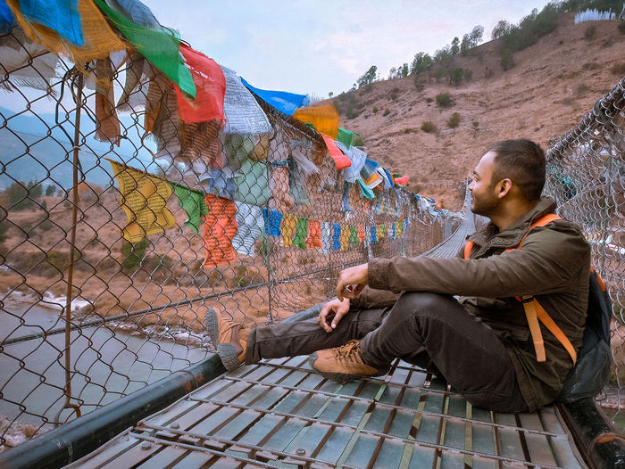 Side view of young man sitting on a suspention bridge with prayer flags outdoors