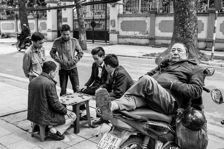 Old man sleeps on a moped as a group of boys play a board game in the background - Hanoi, Vietnam ASIA Bike Board Game Cultures Hanoi Hanoi, Vietnam Men Moped Outdoors Sleeping Street Street Life Street Photography Streetphoto_bw Togetherness Tourism Tourist Destination Travel Travel Photography Vietnam Vietnamphotography