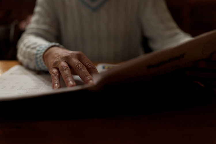 close-up of woman hand holding paper on table Activity Art And Craft Close-up Creativity Hand Holding Human Hand Indoors  Leisure Activity Lifestyles Midsection November One Person Paper Real People Selective Focus Table Women Wood - Material Writing Holiday Moments