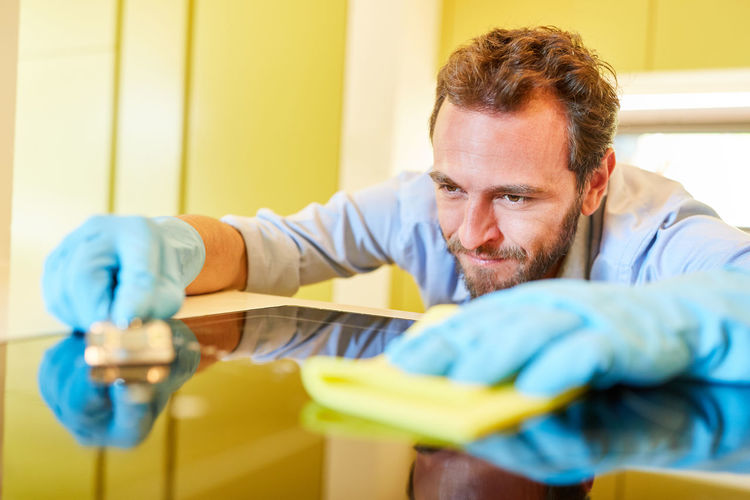 Mid adult man cleaning kitchen counter while contemplating