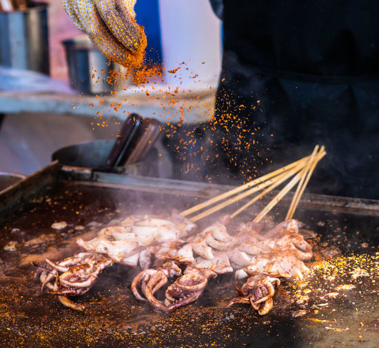 Squid on a skewer being prepared at an evening street festival. BBQ Calamari Cuisine Kiosk Meal Nightphotography Raw Shish Kebabs Barbecue Chef Cooked Festival Flame Food Grilled Hand Motion Night Preparation  Skewer Smoke - Physical Structure Spice Squid Sticks Street Food My Best Photo